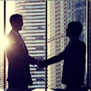 Two businessmen shaking hands. Our therapists offer executive coaching in Chicago for professionals wanting to succeed.