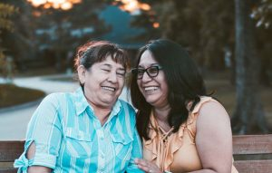A mother and daughter sit close to each other smiling and laughing. They have successfully completed grief counseling with LifePath Counseling in Chicago, IL 60602.