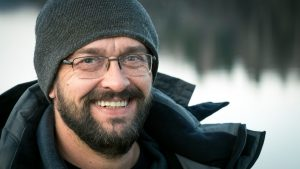 Happy smiling middle-aged bearded man in a knitted hat close-up after Anxiety Treatment and Stress and Depression Therapy from LifePath Therapy in Chicago, IL 60602. You can get help anywhere in the state with online therapy in Illinois too!