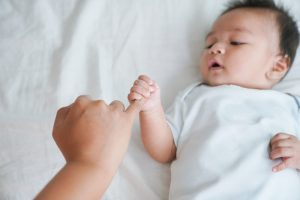 Baby holding a parent's pinky finger laying on its back on a bed. Maternal mental health in Chicago, IL can be supported with postpartum depression treatment at LifePath Therapy in Chicago, IL