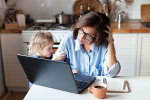 Mother working at the kitchen table with her laptop and a cup of coffee. She looks stressed as her young toddler baby looks on. Maternal mental health matters, and you can get postpartum therapy in Chicago, IL or online counseling in Illinois with LifePath Therapy in Chi.
