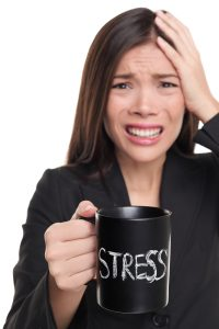 Woman holding a coffee cup with the word stress on it, with the other hand on her head, looking distraught. She could get help with with Anxiety Treatment and Stress and Depression Therapy from LifePath Therapy in Chicago, IL 60602. You can get help anywhere in the state with online therapy in Illinois too!