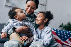 Military mom and two kids smiling and embracing after therapy for maternal overwhelm in Chicago, IL. Maternal mental health in Chicago, IL can be supported with postpartum depression treatment at LifePath Therapy in Chicago, IL 60602 for overwhelmed moms and those feeling overwhelmed.