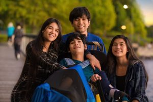 Older Siblings, Brother And Sisters, Surrounding Little Disabled brother needing caregiver support in Chicago, IL. Therapy for caregivers can help you in online therapy in Illinois.